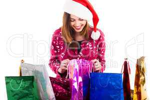 Young girl with santa cap checking into her shopping bags