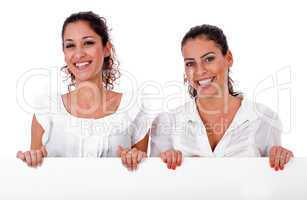 Happy young business colleagues holding a white blank board