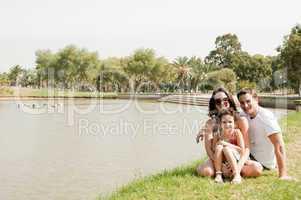 Family sitting near the lake