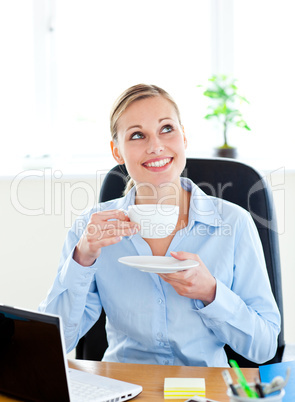 Delighted businesswoman drinking coffee in front of her laptop i