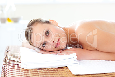 Close-up of a cute woman lying on a massage table with a flower