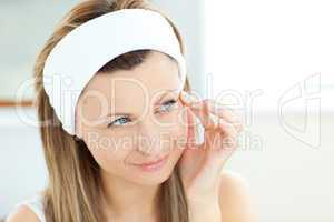 Pretty woman putting cream on her face wearing a headband in the