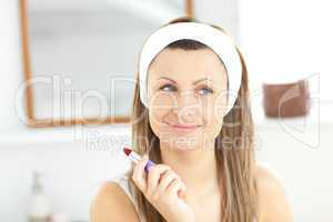 Caucasian young woman using a red lipstick in the bathroom