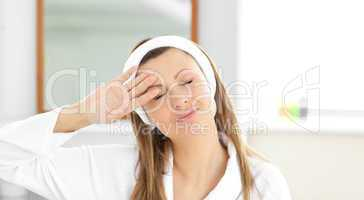 Positive woman putting cream on her face wearing a headband in t