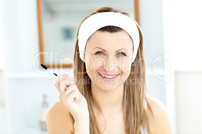Radiant young woman using mascara in the bathroom