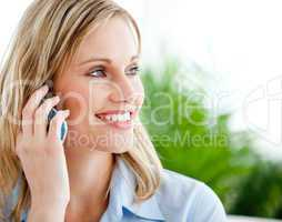 Bright businesswoman talking on phone sitting on a sofa