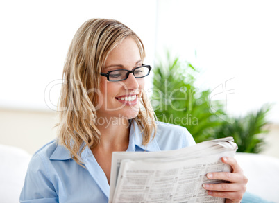 Attractive businesswoman wearing glasses and reading the newspap