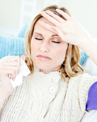 Diseased woman with headache lying on the sofa in the living-roo