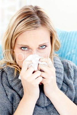 Sick woman using a tissue sitting on a sofa