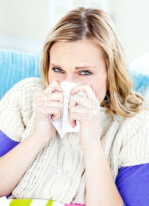 Ill woman using a tissue sitting on a sofa