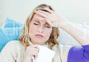 Sick woman with headache lying on the sofa in the living-room