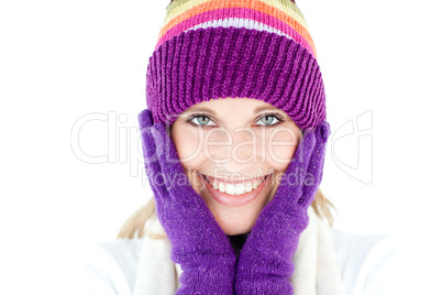 Radiant young woman with cap and gloves in the winter smiling at