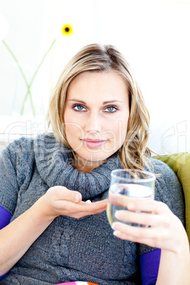 Sick woman taking pills holding a glass of water sitting on a so