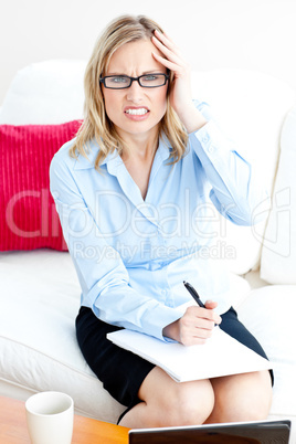 Tired businesswoman writing on her notepad having a headache at