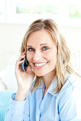 Cheerful businesswoman using her cellphone at home