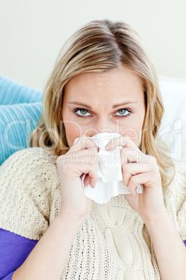 Morbid woman using a tissue sitting on a sofa at home