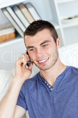 Happy young man talking on phone sitting on a sofa