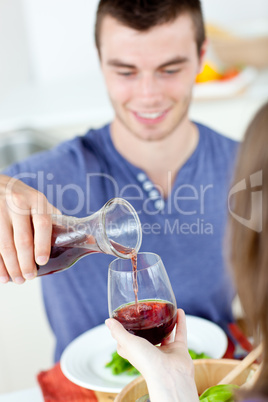 Cute man dining with his girlfriend at home serving her wine