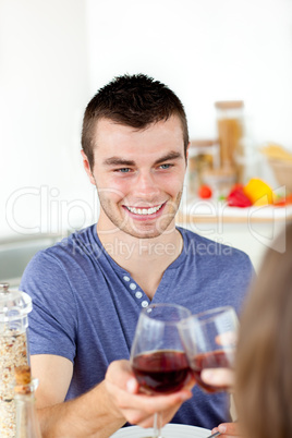Handsome young man having diner with his girlfriend drinking win