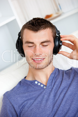 Relaxed young man listening to music with headphones in the livi