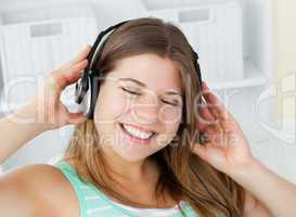 Cheerful young woman listening to music with headphones on a sof