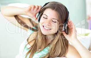 Delighted woman listening to music with headphones on a sofa