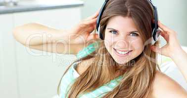 Charming caucasian girl listening to music sitting on a sofa