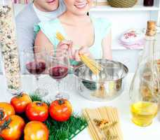 Close-up of an attractive couple cooking spaghetti in the kitche