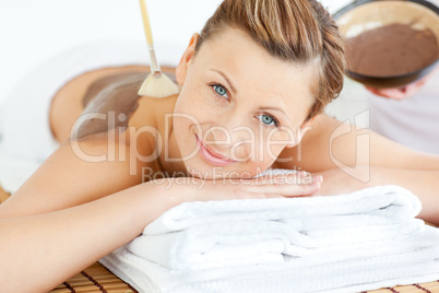 Bright young woman enjoying a beauty treatment with mud