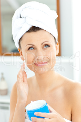 Positive young woman with a towel putting cream on her face in t