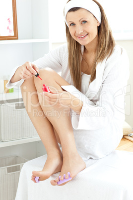 Beautiful young woman varnishing her toenails in the bathroom