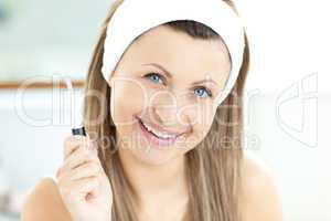 Smiling caucasian woman applying gloss on her lips in the bathro