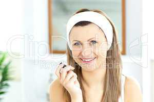Pretty woman applying gloss on her lips in the bathroom