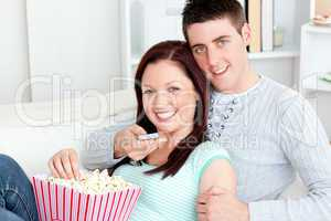 Hugging couple eating popcorn and watching television lying on t