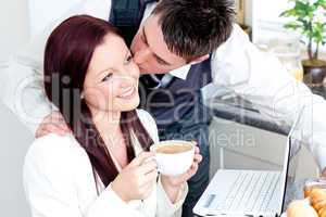 Handsome businessman kissing his bright girlfriend while having