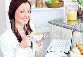 Glowing businesswoman drinking coffee smiling at the camera sitt