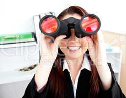 Young businesswoman using binoculars in her office stting at her