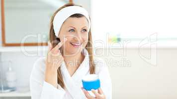 Charming young woman using cream wearing a bath robe in the bath