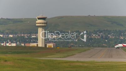 passenger jet taxis past air traffic control tower