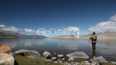Fisherman with spinning catching fish in Khoton Nuur lake