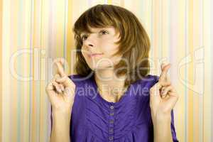 Young woman with fingers crossed