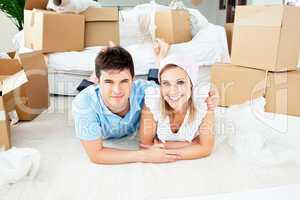Jolly couple lying on the floor between boxes