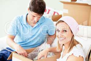 Ambitious young couple unpacking boxes with glasses