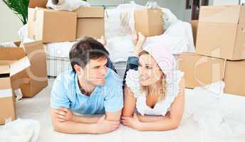 Young couple lying on the floor after unpacking boxes