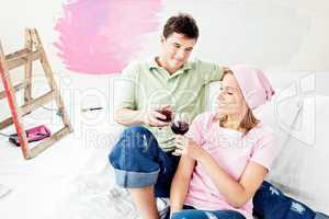 Delighted caucasian couple lying on a sofa and drinking wine aft