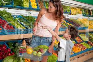 Grocery store shopping - Woman with child buying vegetable