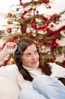 Young woman sitting in front of Christmas tree
