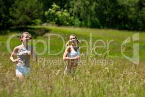 Two young woman jogging in a meadow