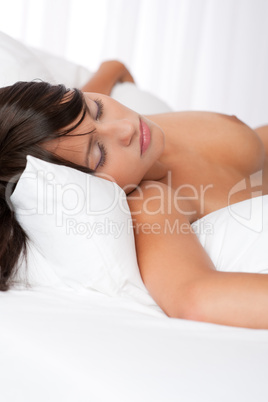 Naked woman sleeping naked in white bed