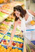 Grocery store - smiling woman shopping choose fruit